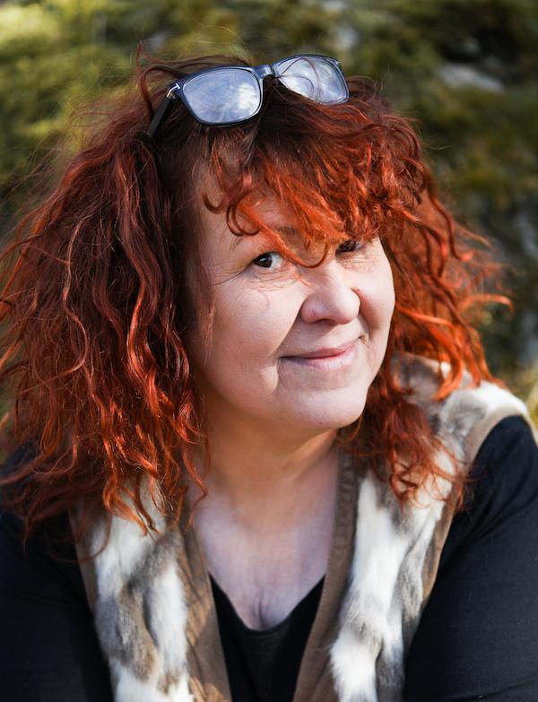 Punahiuksinen Paula Huhtanen katsoo kohti suoraan ja avoimesti, pieni hymynkare huulilla.