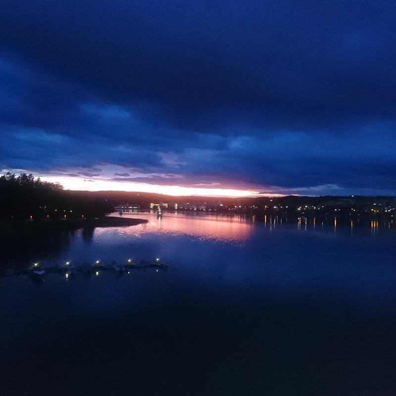 Tummansininen maisemakuva satamasta. Illankajo hehkuu horisontissa ja heijastuu veden pinnasta.