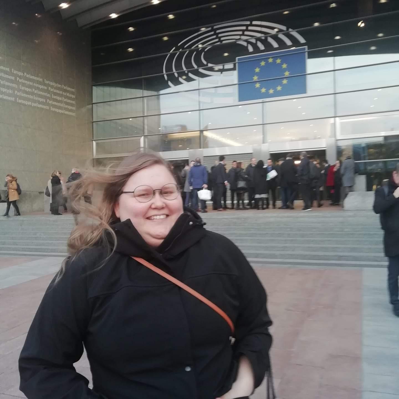 Hymyilevä Fanni-Laura Mäntylä seisoo Euroopan Unionin parlamentin sisäänkäynnin edessä. Tuuli heiluttaa pitkiä ruskeita hiuksia.