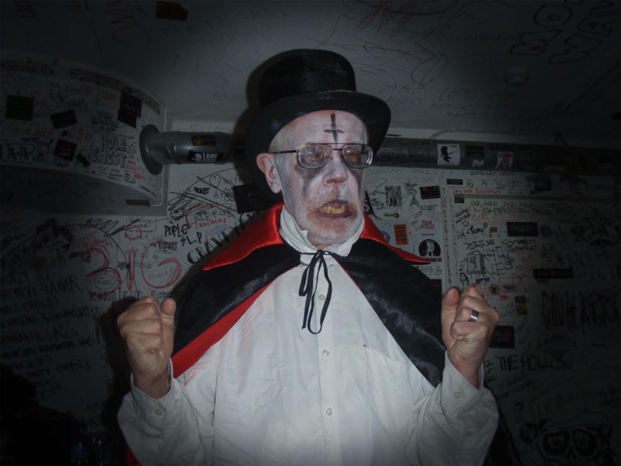 Taiteilija Kalevi Helvetti irvistää kädet nyrkissä. Hänellä on yllään musta silinterihattu ja viitta. Kasvot on maskeerattu valkoisella värillä, silmät mustattu ja otsalle on piirrety musta alaspäin oleva risti.