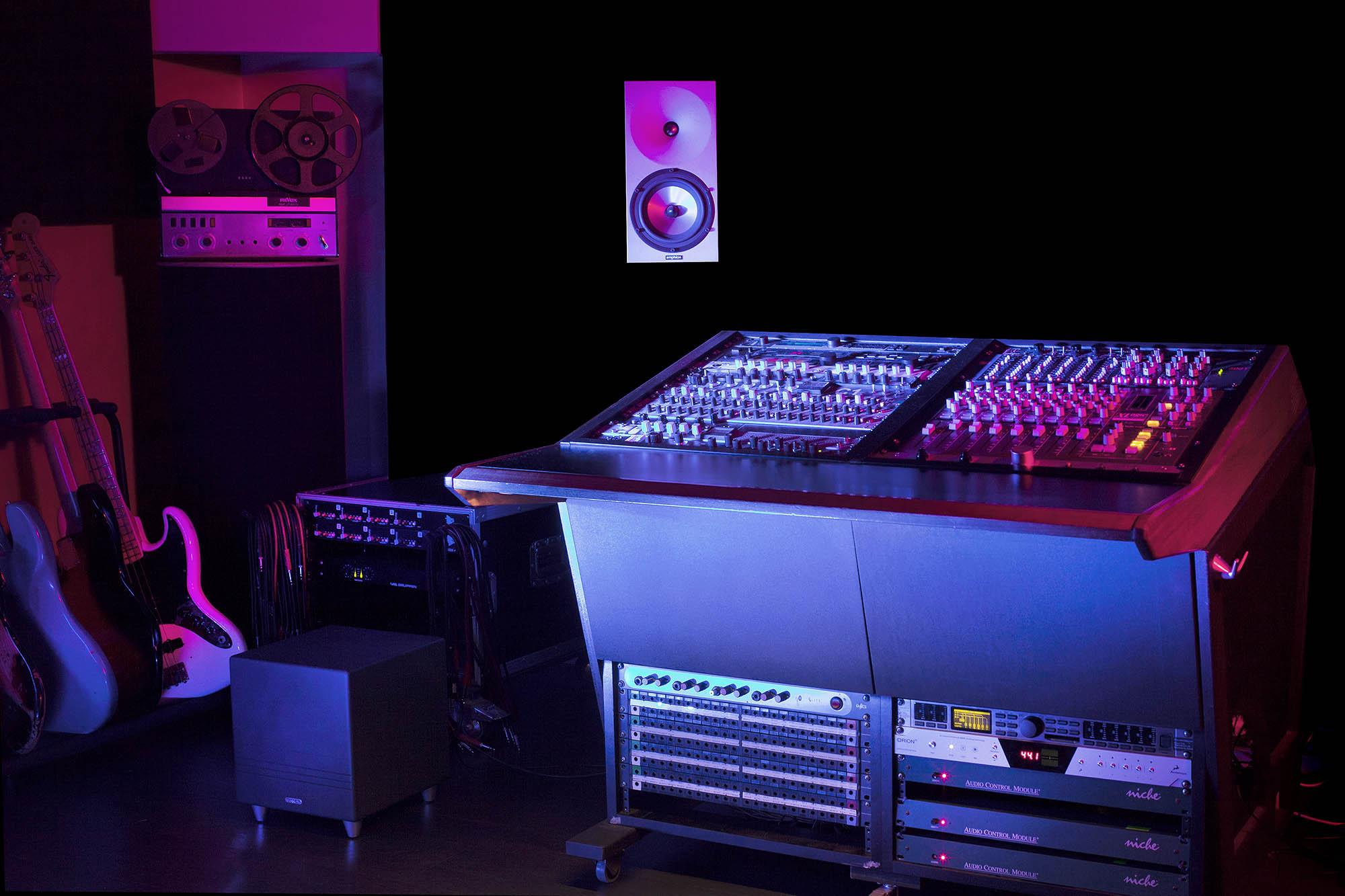 Pimeä, sini-punaisilla värivaloilla valaistu studio, jossa on miksauspöytä, kaiutin, nauhuri ja kitaroita rivissä seinustalla.