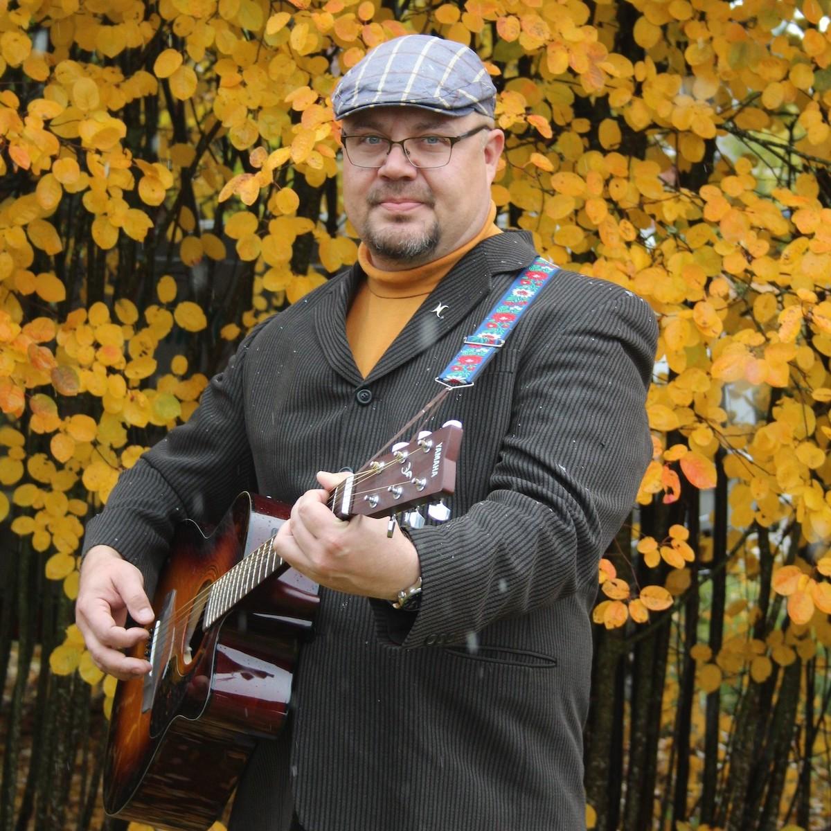 Muusikko Harri Andersson soittaa akustista kitaraa ulkona, kirkkaankeltaisen syksyisen pensaikon edessä. Hän katsoo lempeästi kohti. Hänellä on lakki ja pikkutakki sekä ruskan sävyyn sointuva poolopusero.