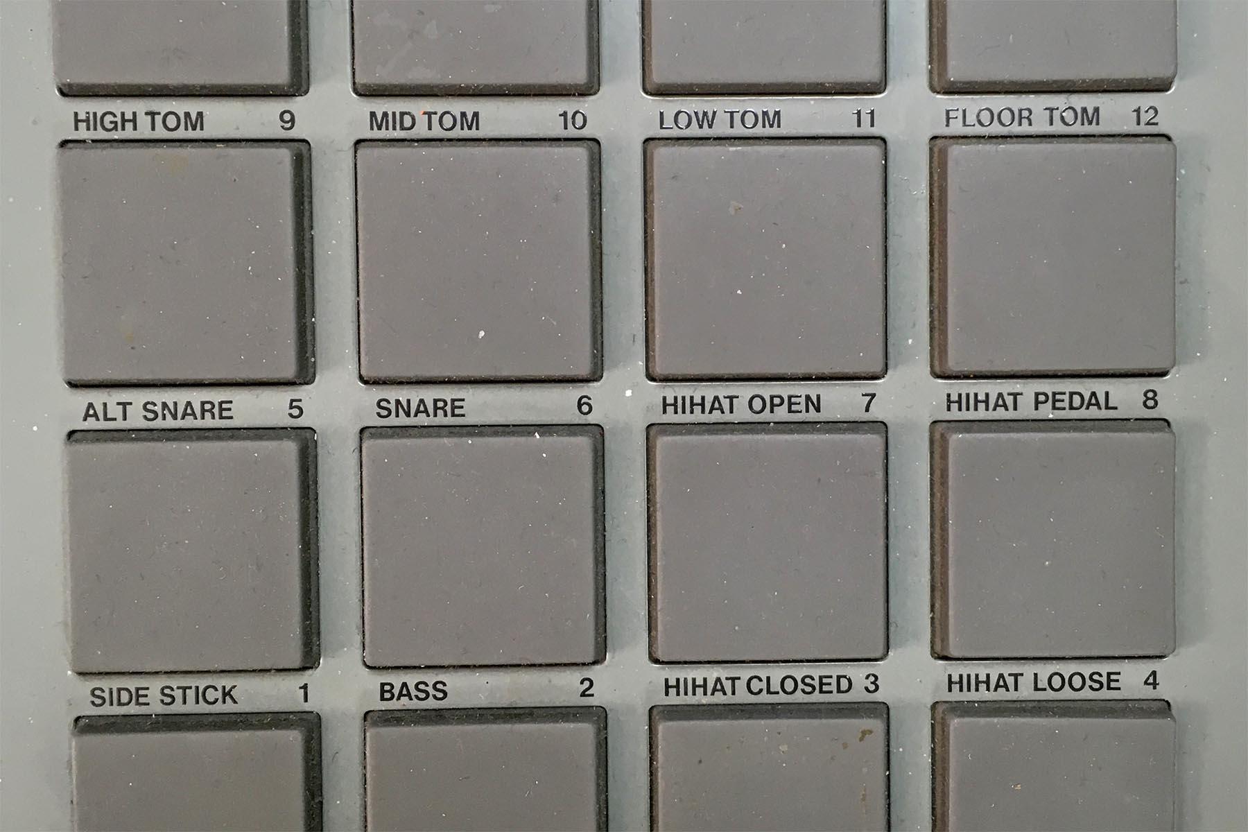 Harmaa MPC-rumpukoneen näppäinruudukko. Joka näppäimen yllä lukee teksti, esimerkiksi mid tom, snare, hihat open, side stick tai bass.