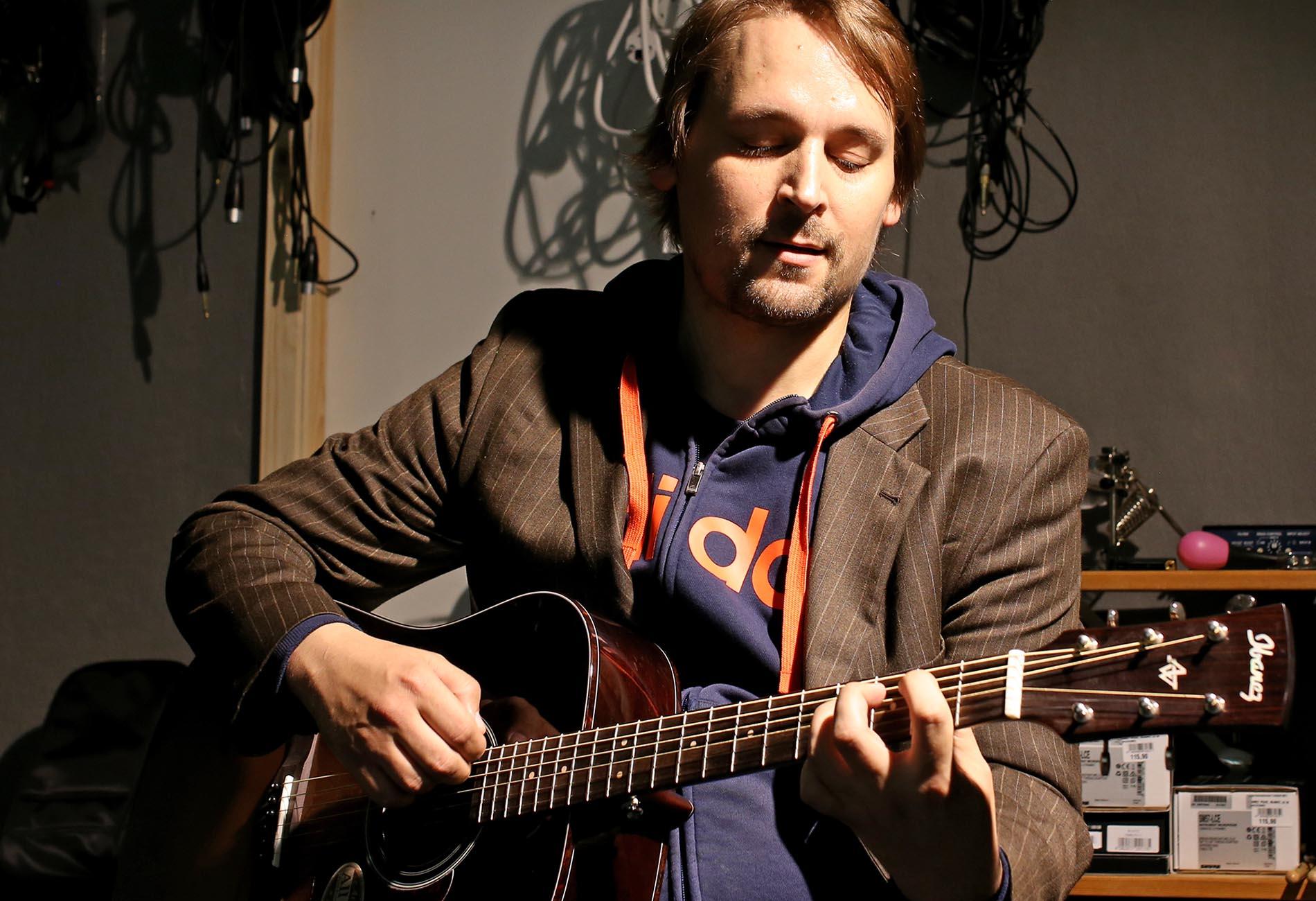 Kare Poutanen näppäilee keskittyneenä akustista kitaraa studiossa.