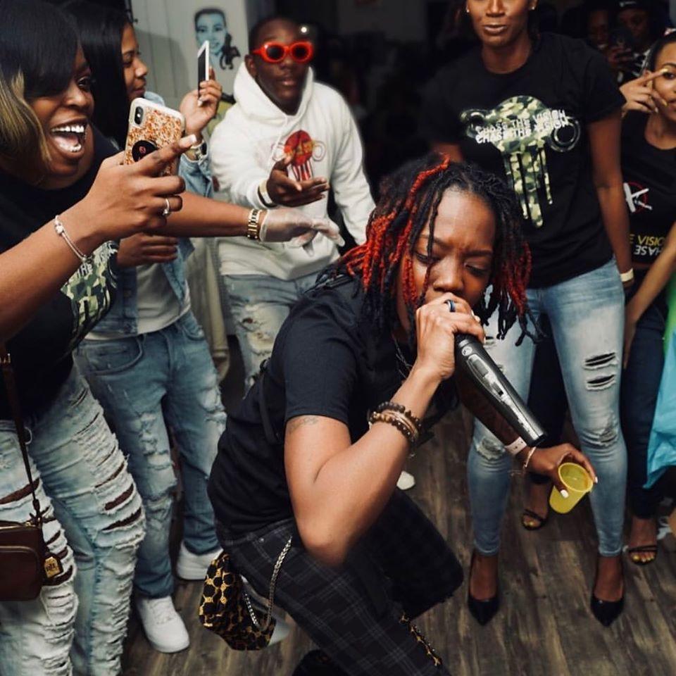 Tummaihoinen naisartisti räppää puristaen mikrofonia lähellä suutaan. Ympärillä väkijoukko tanssii.