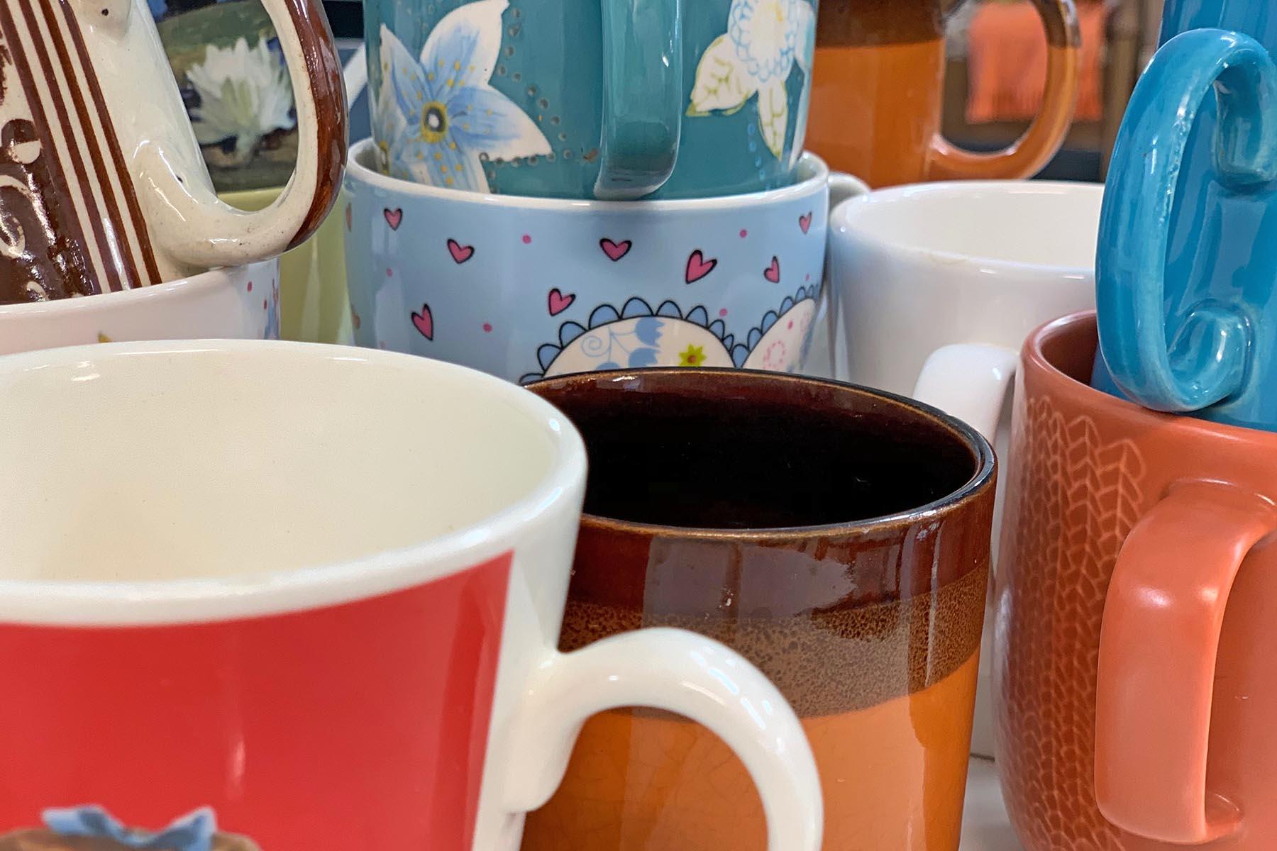 Kaikenvärisiä kahvikuppeja sekalaisessa rykelmässä.