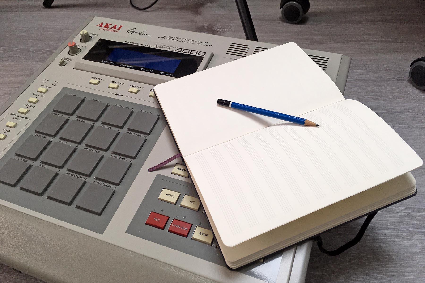 Studiossa MPC-rumpukoneen päällä on avonainen muistivihko ja lyijykynä.