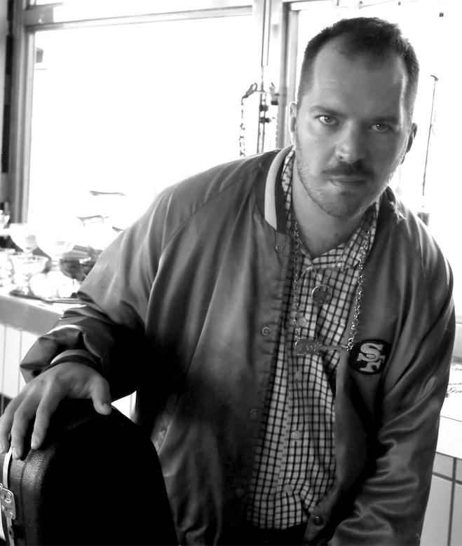 Mustavalkokuvassa muusikko Riku Turpeinen nojaa kitarakoteloon ja katsoo kohti.