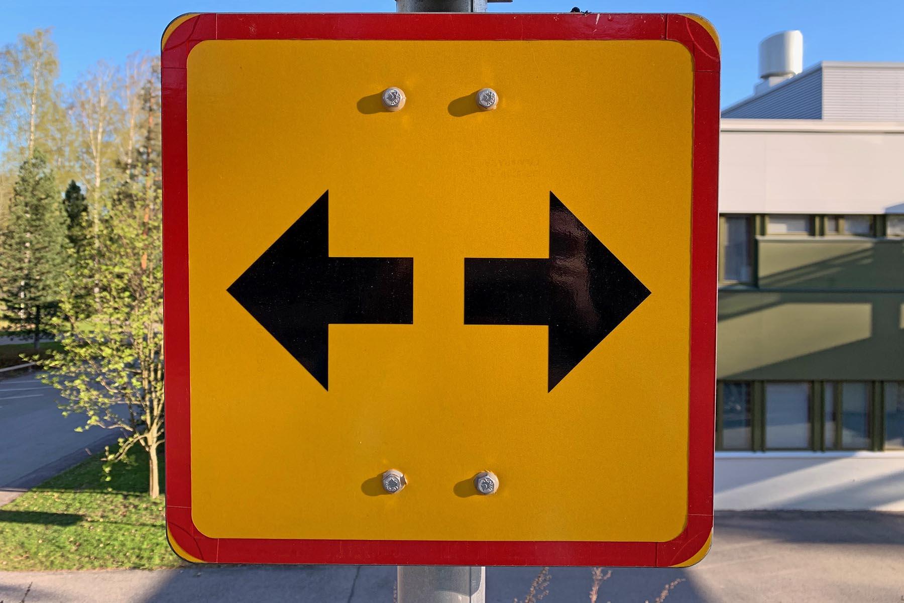 Keltaisessa liikennemerkissä on kaksi mustaa nuolta, toinen osoittaa vasemmalle ja toinen oikealle.