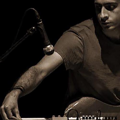 Miesartisti, kitara kaulallaan, on kumartunut säätämään pöydällä olevia kitaran efektipedaaleja.
