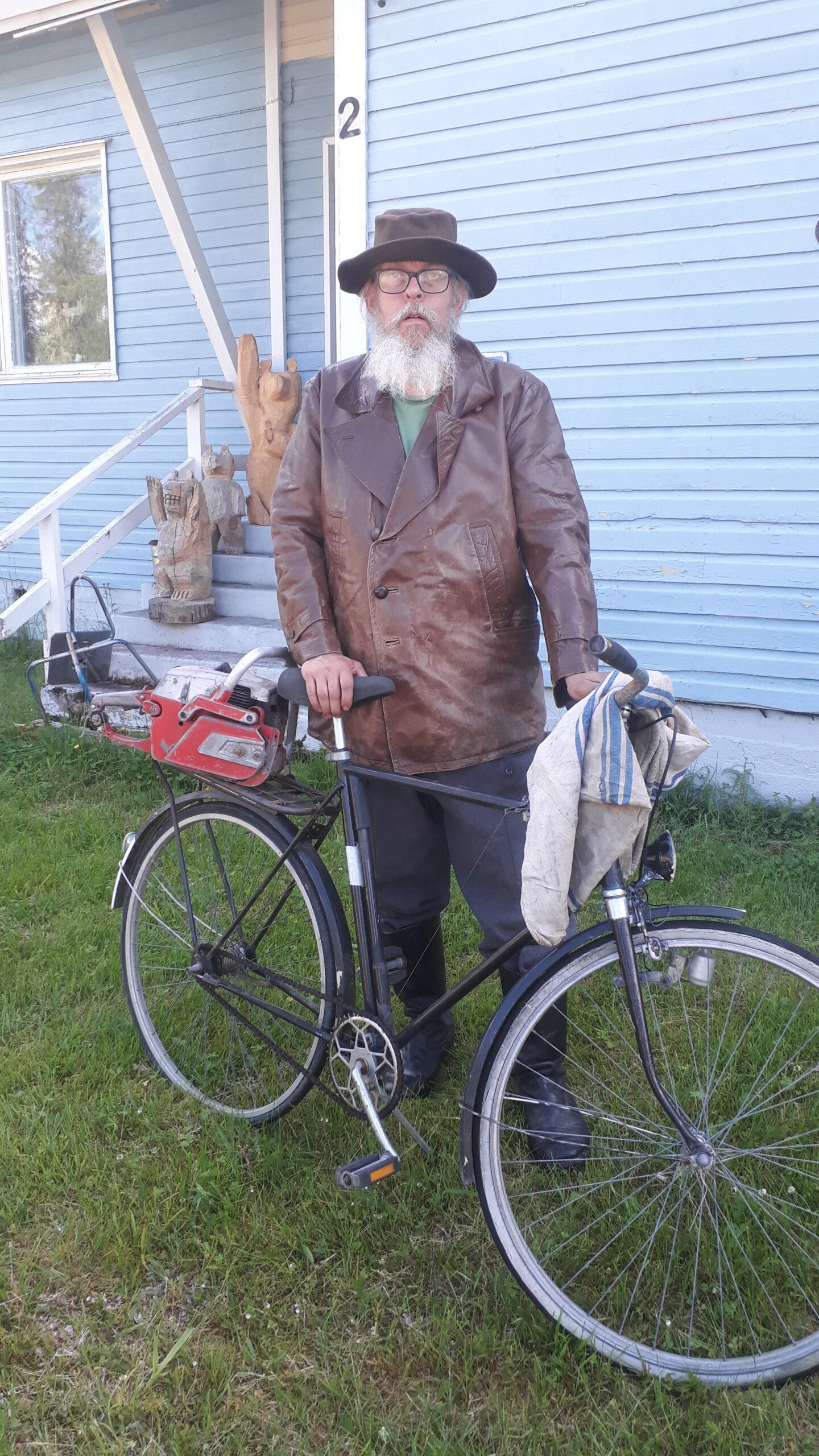 Ruskeaan nahkatakkiin ja lierihattuun pukeutunut mies katsoo kohti. Hänellä on pitkä harmaa parta. Hän seisoo talon edessä polkupyörään nojaten. Takana näkyy puuveistoksia talon portailla.