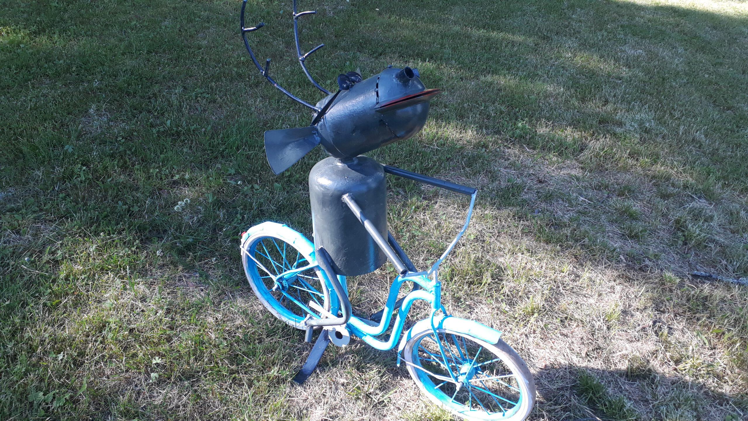 Metallitangoista, lieriöistä ja putkista on rakennettu musta, sarvipäinen hirveä muistuttava eläinhahmo. Se istuu sinisen lasten polkupyörän satulassa kuin polkisi sitä vauhdikkaasti.