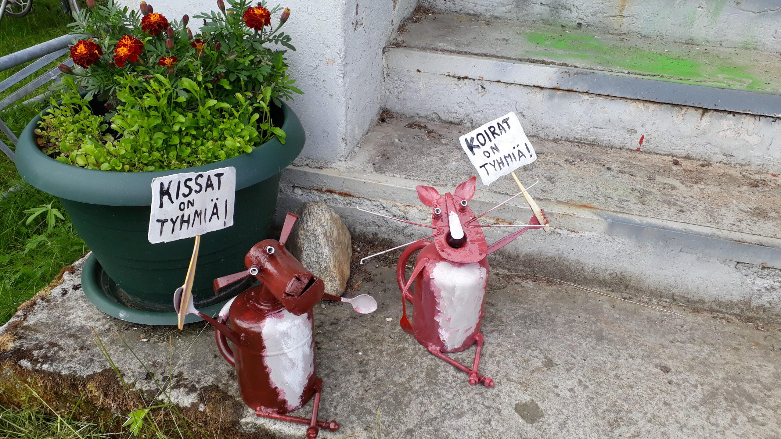 """Portaanpielessä kaksi punaista metallikappaleista muotoiltua eläinhahmoa pitelee kylttejä. Suu ammollaan olevan kissan kyltissä lukee """"Koirat on tyhmiä!"""". Koiran kyltissä lukee """"Kissat on tyhmiä!""""."""