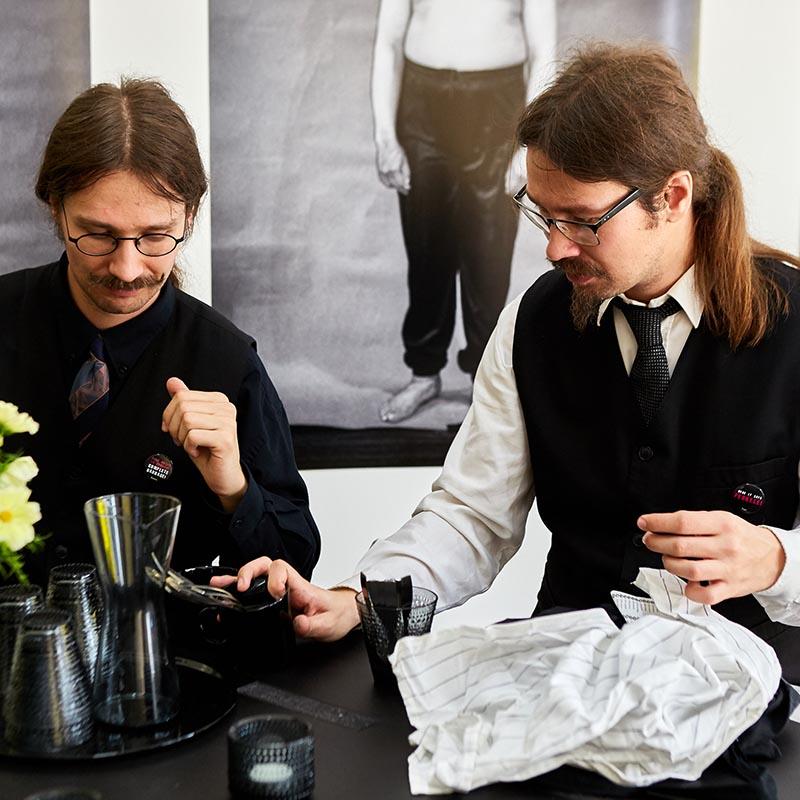 Niklas ja Joonas Nyholm pöydän ääressä ottamassa juomia. He muistuttavat ulkonäöltään toisiaan: molemmilla on pitkät ruskeat hiukset, viikset, silmälasit ja kravatit.