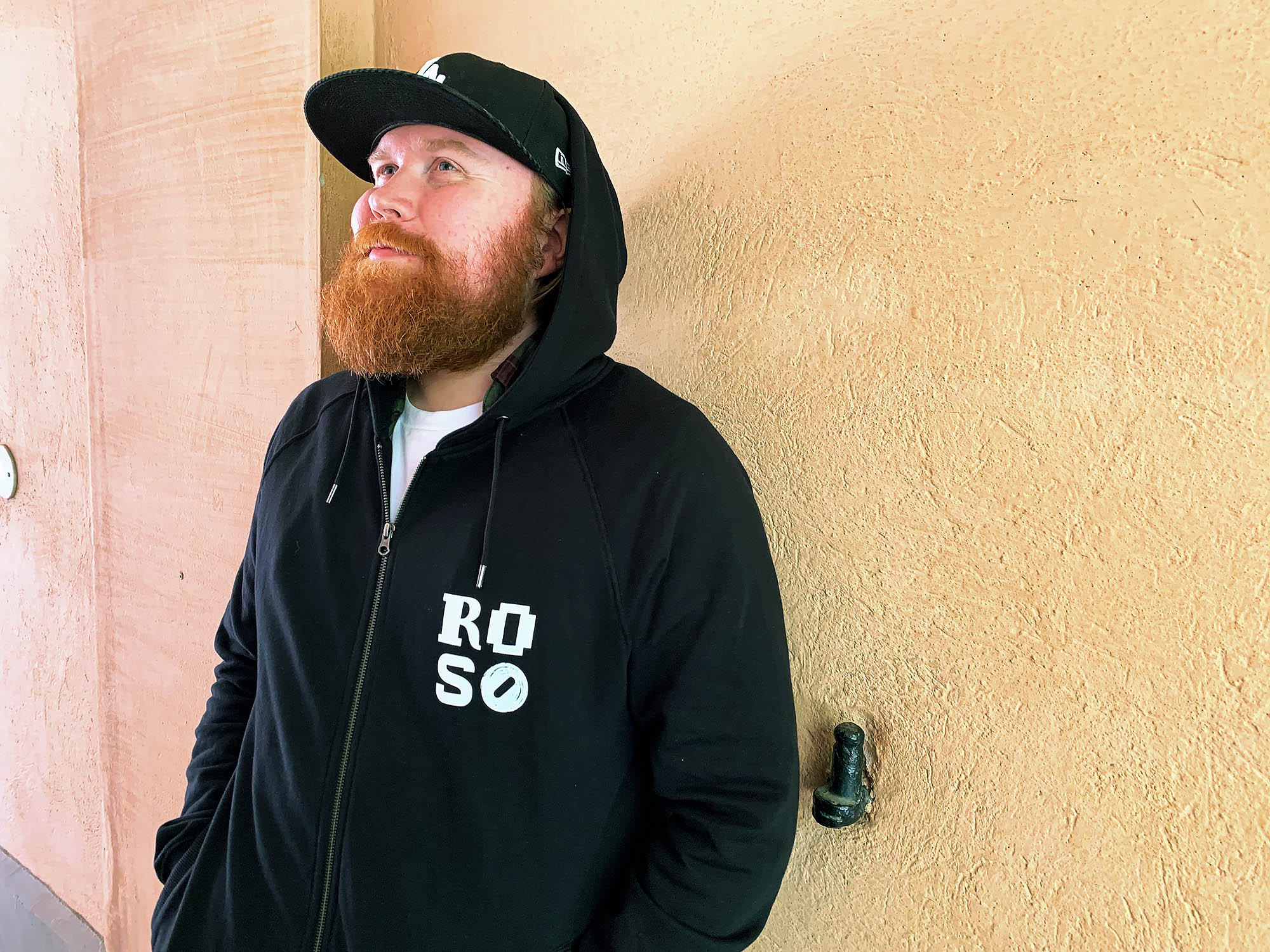 Punapartainen, kolmikymppinen ja mustaan Roso-logolla varustettuun huppariin pukeutunut mies nojailee kellanväriseen seinään porttikäytävässä. Hän katselee mietteliäänä yläviistoon.