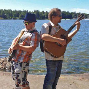 Kaksi miestä soittavat kitaroita selät vastakkain. Vasemmanpuoleisella on sähkökitara ja sininen lierihattu. Oikeanpuoleinen, parrakas mies soittaa akustista kitaraa.