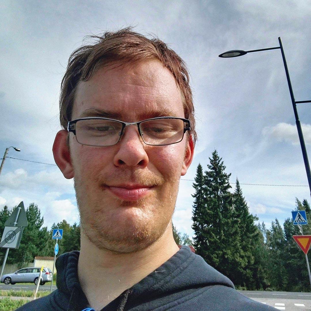 Selfiessä parikymppinen, silmälasipäinen mies, jolla on rauhallinen ilme ja katse alaspäin.