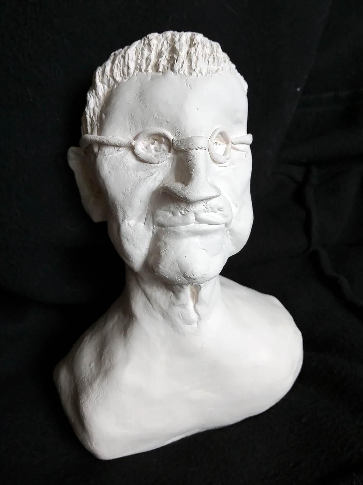 Valkoinen, massasta muotoiltu rintakuva esittää lyhythiuksista, silmälasipäistä miestä. Hänellä on soikeat kasvot, suora nenä ja korkea otsa.