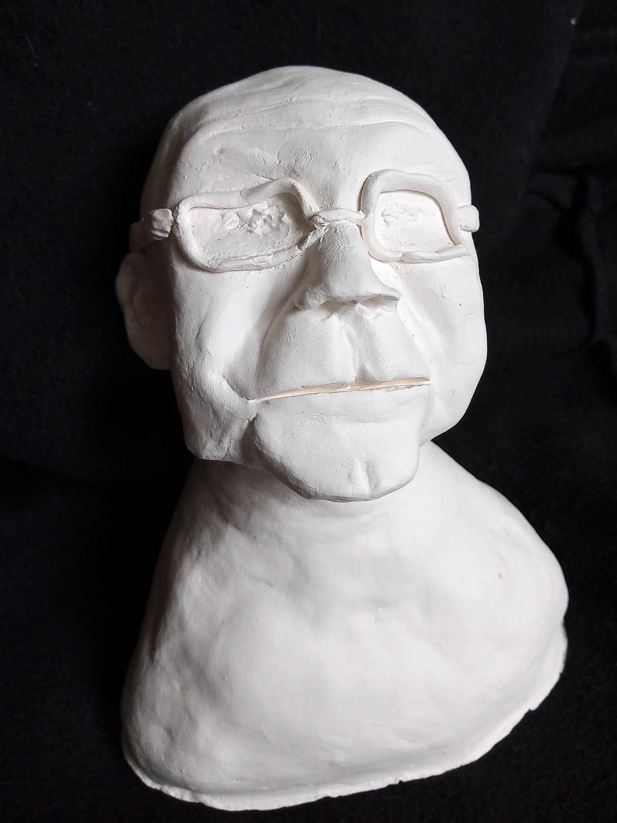 Valkoinen, massasta muotoiltu rintakuva esittää kaljua, silmälasipäistä miestä. Hänellä on pyöreät kasvot, leveä suu ja suuret paksusankaiset silmälasit.