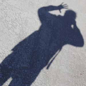 Selfiekuvassa miehen musta varjokuva heijastuu maahan ja vilkuttaa.
