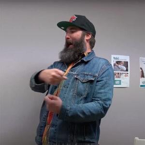 Videon pysäytyskuvassa lippispäinen, tuuheapartainen mies puhuu ja viittilöi jollekulle.
