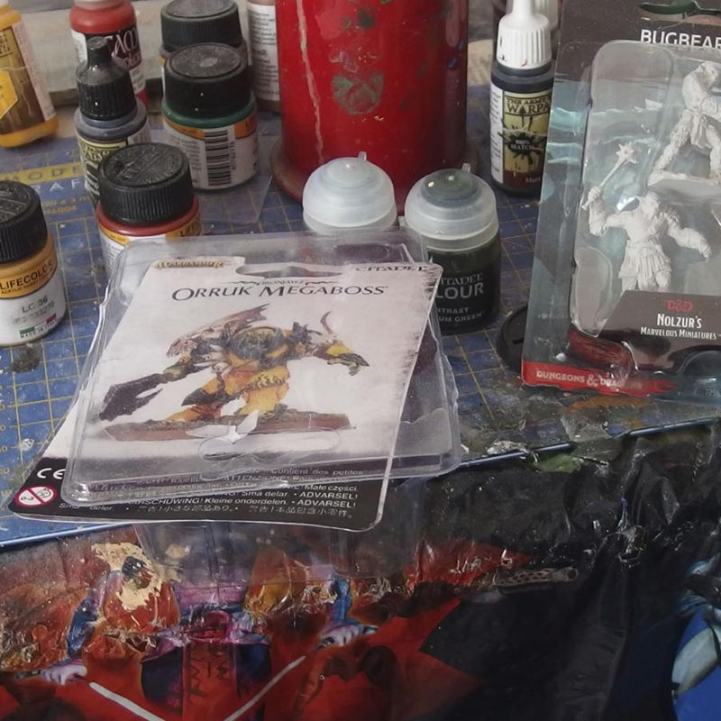 Työpöydällä on soturi-figuriineja ja erilaisia maalipurkkeja.