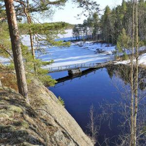 Luontomaisema. Jyrkän kallion laelta on näkymä alas järvelle. Kävelysilta ylittää pienen salmen. Maassa on paikoin lunta ja järvessä jäätä.